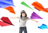 Cute little pilot among colorful paper planes — Stock Photo