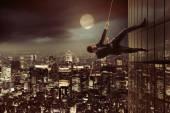 Ambitious businessman climbing on the skyscraper — Stock Photo