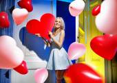 Portrait of an attractive woman with bunch of balloons — Stock Photo