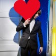 Handsome man carrying a large heart — Stock Photo #64712809
