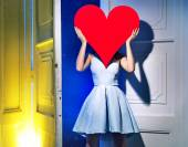 Woman hiding herself behind a heart — Stock Photo