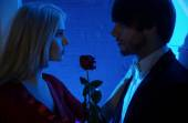 Red rose between people in love — Stock Photo