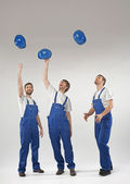 Young tired builders throwing helmets — Stock Photo