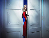 Blond woman carefully opening the door — Stock Photo