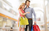Young couple with a bunch of shopping bags — Stock Photo