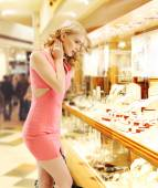 Pretty lady looking at the shop window — Stock Photo
