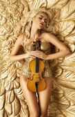 Conceptual picture of golden woman holding a violin — Stock Photo