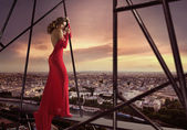 Elegant lady standing on the edge of the roof — Stock Photo