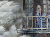 Portrait of an amazing woman standing on lighhouse during the st — Stock Photo