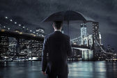 Young businessman with an umbrella over the night city backgroun — Stock Photo