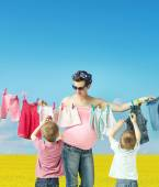 Mom doing the laundry with sons — Stock Photo