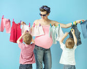 Mom doiing the laundry with her sons — Stock Photo