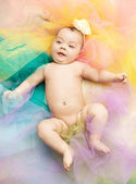 Cute little toddler lying on colorful floor — Stock Photo