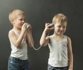 Cute little brothers talking on the toy phone — Stock Photo