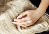 Straight blond wig brushing by a woman — Stockfoto