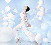 Fashion shot of adorable woman in studio full of balloons — Stock Photo