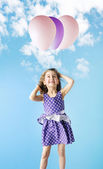 Little girl holding colorful balloons — Stock Photo