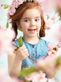 Cheerful litlle girl holding a branch — Stock Photo