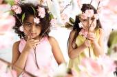 Two cute grils hiding herself behind branches — Stock Photo