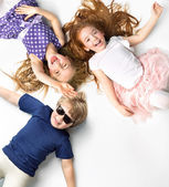 Portrait of siblings lying on a white background  — Stock Photo