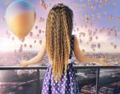 Little girl looking at the thousands of balloons — Stock Photo