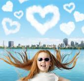 Ginger girl and heart-shaped cllouds — Stock Photo