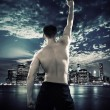 Muscular athlete over the city background — Stock Photo #74054831