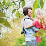 Cheerful couple walking among apple-trees — Stock Photo #74088149