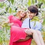 Joyful couple in the fragrant orchard — Stock Photo #74088603