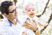 Cheerful father holding his lovely baby — Stock Photo