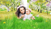 Mother and child lying on the fresh lawn — Stock Photo