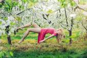 Adorable slim lady levitating in the orchard — Stock Photo