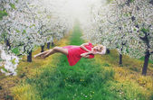 Majestic slim nymph levitating in the orchard — Stock Photo