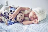 Newborn child sleeping with a teddy bear — Stock Photo