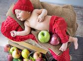 Newborn child sleeping on the box of apples — Stock Photo