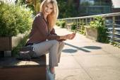 Adorable woman sitting on the public bench — Stock Photo
