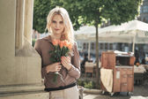 Portrait of a young blond woman with a bunch of roses — Stock Photo