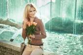 Blond lady sitting next to the fountain — Stock Photo