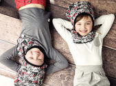 Cheerful siblings lying on the wooden floor — Stock Photo