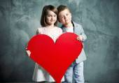 Two kids holding a giant heart — Stock Photo