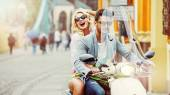 Handsome man riding a scooter with lauging girl — Stock Photo
