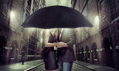 Young couple hiding themselves under the umbrella — Stock Photo