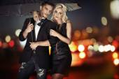 Smart couple walking with the umbrella — Stock Photo