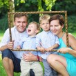 Portrait of the young family posing in the garden — Stock Photo #77500288