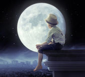 Little boy looking a the city in the night — Stock Photo