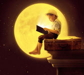 Cute little boy reading a book in the moon light — Stock Photo