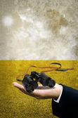 Binocular in businessman hand with field background in retro sty — Stock Photo