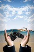 Verrekijker in hand op strand — Stockfoto