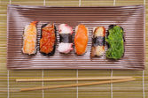 Sushi nigiri, Japanese cuisine with bamboo sticks — Stock Photo
