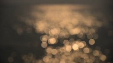 Bokeh of sunset light reflect on wave at sea (Blurred background) — Stock Video
